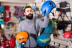 Νέος αρσενικός πελάτης που εξετάζει τα κράνη στο κατάστημα αθλητικού εξοπλισμού Στοκ εικόνες με δικαίωμα ελεύθερης χρήσης