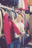 Νέος αρσενικός πελάτης που εξετάζει τα παλτά Στοκ φωτογραφία με δικαίωμα ελεύθερης χρήσης