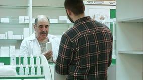 Νέος αρσενικός πελάτης που παίρνει τη φουσκάλα των χαπιών από το φαρμακοποιό στο φαρμακείο απόθεμα βίντεο