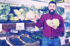 Νέος αρσενικός πωλητής που προσφέρει τα κουνουπίδια Στοκ Εικόνες