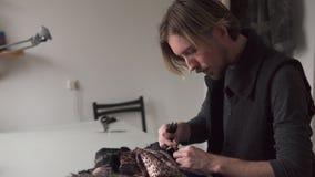 Νέος αρσενικός ράφτης που εργάζεται furrier στο εργαστήριο φιλμ μικρού μήκους