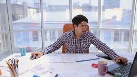 Νέος αρχιτέκτονας, επιχειρηματίας στο σύγχρονο φωτεινό γραφείο που λειτουργεί στον υπολογιστή με το σχεδιάγραμμα και σχέδια απόθεμα βίντεο