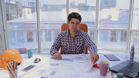 Νέος αρχιτέκτονας, επιχειρηματίας στο σύγχρονο φωτεινό καθαρό γραφείο που λειτουργεί με το σχεδιάγραμμα και σχέδια απόθεμα βίντεο