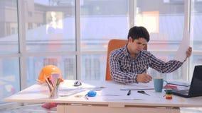 Νέος αρχιτέκτονας που εργάζεται με τα σχεδιαγράμματα στο γραφείο φιλμ μικρού μήκους