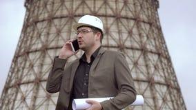 Νέος αρχιτέκτονας στο υπόβαθρο του σταθμού παραγωγής ηλεκτρικού ρεύματος ελκυστικός αρσενικός σχεδιαστής που κρατά ένα στρέθιμο τ απόθεμα βίντεο