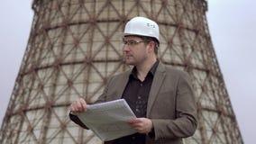 Νέος αρχιτέκτονας στο υπόβαθρο του σταθμού παραγωγής ηλεκτρικού ρεύματος ελκυστικός αρσενικός σχεδιαστής που κρατά ένα σχέδιο Δρο απόθεμα βίντεο