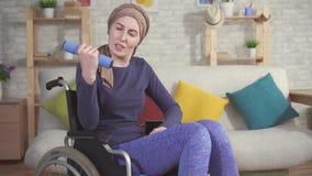 Νέος ασθενής με καρκίνο γυναικών σε μια αναπηρική καρέκλα στο μαντίλι μια αποκατάσταση μετά από τη χημειοθεραπεία κοντά επάνω απόθεμα βίντεο