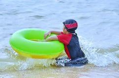 Νέος Ασιάτης κάθεται στην κυματωγή σε μια ωκεάνια παραλία με doughnut της στοκ εικόνα