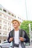 Νέος Ασιάτης που ταξιδεύει backpacker έχοντας τη διασκέδαση στην πόλη Στοκ Εικόνες