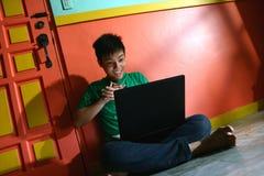 Νέος ασιατικός έφηβος με έναν φορητό προσωπικό υπολογιστή σε ένα καθιστικό Στοκ Φωτογραφία