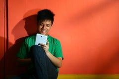 Νέος ασιατικός έφηβος με μια ταμπλέτα σε ένα καθιστικό Στοκ Εικόνα
