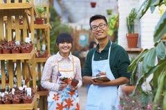 Νέος ασιατικός ανθοκόμος δύο που εργάζεται στο κατάστημα στοκ φωτογραφία