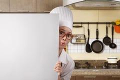 Νέος ασιατικός αρχιμάγειρας γυναικών που στέκεται από πίσω από το λευκό πίνακα Στοκ Εικόνα