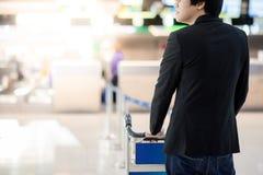 Νέος ασιατικός επιχειρηματίας με το καροτσάκι στο τερματικό αερολιμένων Στοκ Φωτογραφίες
