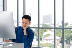 Νέος ασιατικός επιχειρηματίας που εξετάζει τη οθόνη υπολογιστή Το πρόσωπό του στοκ εικόνες