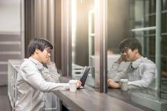 Νέος ασιατικός επιχειρηματίας που εργάζεται με το lap-top στον καφέ Στοκ Εικόνες