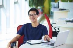 Νέος ασιατικός επιχειρηματίας που εργάζεται στο γραφείο στοκ φωτογραφία