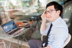 Νέος ασιατικός επιχειρηματίας που κρατά ένα ρολόι στη δυσάρεστη έκφραση προσώπου - έννοια επιχειρήσεων και χρόνου Στοκ Φωτογραφίες