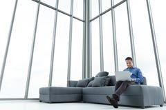 Νέος ασιατικός επιχειρηματίας που χρησιμοποιεί τη συνεδρίαση σημειωματάριων στον καναπέ Ευτυχές sm στοκ φωτογραφία με δικαίωμα ελεύθερης χρήσης