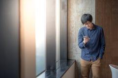 Νέος ασιατικός επιχειρηματίας που χρησιμοποιεί το έξυπνο τηλέφωνο Στοκ εικόνα με δικαίωμα ελεύθερης χρήσης