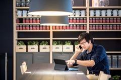 Νέος ασιατικός επιχειρηματίας που χρησιμοποιεί το smartphone και την ταμπλέτα στο ομο workin Στοκ Εικόνες