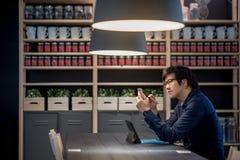 Νέος ασιατικός επιχειρηματίας που χρησιμοποιεί το smartphone και την ταμπλέτα στο ομο workin Στοκ φωτογραφία με δικαίωμα ελεύθερης χρήσης