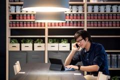 Νέος ασιατικός επιχειρηματίας που χρησιμοποιεί το smartphone και την ταμπλέτα στο ομο workin Στοκ εικόνα με δικαίωμα ελεύθερης χρήσης