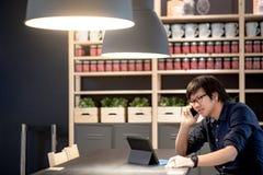 Νέος ασιατικός επιχειρηματίας που χρησιμοποιεί το smartphone και την ταμπλέτα στο ομο workin Στοκ φωτογραφίες με δικαίωμα ελεύθερης χρήσης
