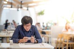 Νέος ασιατικός επιχειρηματίας που χρησιμοποιεί το smartphone στο εστιατόριο Στοκ φωτογραφίες με δικαίωμα ελεύθερης χρήσης