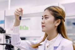 Νέος ασιατικός ερευνητής που εξετάζει τη φιάλη στην εργασία επιστήμης Στοκ εικόνα με δικαίωμα ελεύθερης χρήσης
