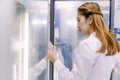 Νέος ασιατικός ερευνητής που εξετάζει τη φιάλη στην εργασία επιστήμης Στοκ Φωτογραφίες