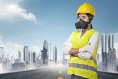 Νέος ασιατικός θηλυκός εργάτης οικοδομών με το κίτρινο κράνος και Η.Ε Στοκ Φωτογραφία