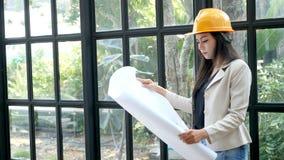 Νέος ασιατικός θηλυκός μηχανικός κατασκευής σχεδιαγράμματα στα κίτρινα σκληρά ασφάλειας κρανών καπέλων εκμετάλλευσης αρχιτεκτόνων απόθεμα βίντεο