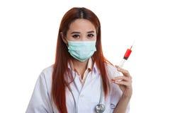 Νέος ασιατικός θηλυκός γιατρός με τη σύριγγα λαβής μασκών Στοκ Εικόνες