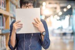 Νέος ασιατικός σπουδαστής ατόμων που ανυψώνει το άσπρο βιβλίο στη βιβλιοθήκη στοκ εικόνα με δικαίωμα ελεύθερης χρήσης