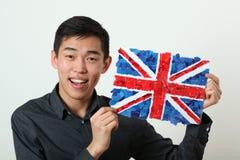 Νέος ασιατικός σπουδαστής που παρουσιάζει βρετανική εθνική σημαία Στοκ φωτογραφία με δικαίωμα ελεύθερης χρήσης