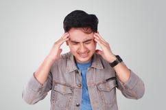 Νέος ασιατικός τύπος που υφίσταται τον πονοκέφαλο στοκ εικόνα