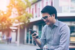 Νέος ασιατικός όμορφος επιχειρηματίας που χαμογελά διαβάζοντας έξυπνό του Στοκ Φωτογραφίες
