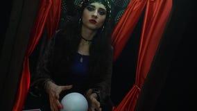 Νέος αφηγητής τύχης brunette με τα κόκκινα καρφιά, που δημιουργούν με μια σφαίρα κρυστάλλου απόθεμα βίντεο