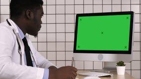 Νέος αφρικανικός γιατρός σε μια συνεδρίαση παλτών εργαστηρίων στο γραφείο του και τη λήψη μερικών σημειώσεων εξετάζοντας τη οθόνη απόθεμα βίντεο