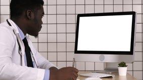 Νέος αφρικανικός γιατρός σε μια συνεδρίαση παλτών εργαστηρίων στο γραφείο του και τη λήψη μερικών σημειώσεων εξετάζοντας τη οθόνη φιλμ μικρού μήκους