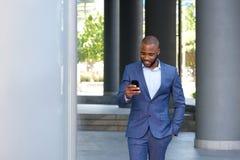 Νέος αφρικανικός επιχειρηματίας που περπατά και που εξετάζει το κινητό τηλέφωνο Στοκ φωτογραφία με δικαίωμα ελεύθερης χρήσης