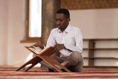Νέος αφρικανικός μουσουλμανικός τύπος που διαβάζει το Koran Στοκ φωτογραφία με δικαίωμα ελεύθερης χρήσης