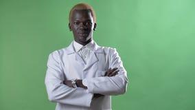 Νέος αφρικανικός ξανθός γιατρός στο άσπρο παλτό και γυαλιά που εξετάζουν τη κάμερα, που στέκεται μόνο στο υπόβαθρο chromakey απόθεμα βίντεο