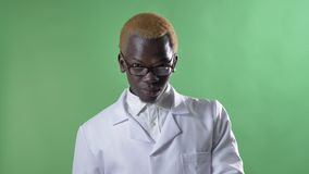 Νέος αφρικανικός ξανθός γιατρός στο άσπρο παλτό σχετικά με τα γυαλιά του και εξέταση τη κάμερα, που απομονώνεται στο βασικό υπόβα φιλμ μικρού μήκους