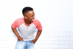 Νέος αφρικανικός τύπος που γελά ενάντια στον άσπρο τοίχο Στοκ εικόνα με δικαίωμα ελεύθερης χρήσης
