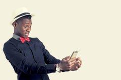 Νέος αφρικανικός τύπος που εξετάζει το τηλέφωνο κυττάρων Στοκ φωτογραφία με δικαίωμα ελεύθερης χρήσης