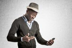Νέος αφρικανικός τύπος που εξετάζει το τηλέφωνο κυττάρων Στοκ Εικόνες