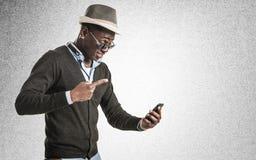 Νέος αφρικανικός τύπος που εξετάζει το τηλέφωνο κυττάρων Στοκ Εικόνα