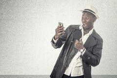 Νέος αφρικανικός τύπος που εξετάζει το τηλέφωνο κυττάρων Στοκ Φωτογραφία